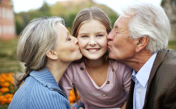 Бабушка и дедушка целуют внучку