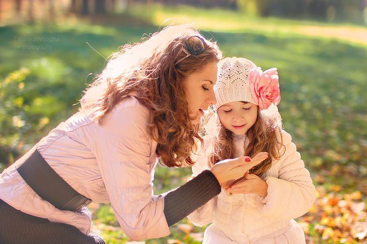 Мама и дочь гуляют в парке