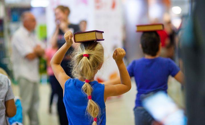 Дети носят книги на голове